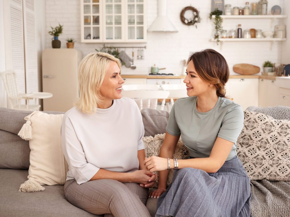 Beautiful happy mature mother and her adorable cute daughter spending time together after long separation, sitting in cozy living room interior and talking, looking at each other and smiling