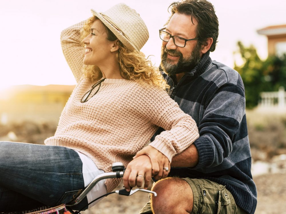 Happy youthful couple enjoy the bike ride together man carrying woman and both laughing and have fun - active and cheerful people in love at middle age concept - sunlight in background